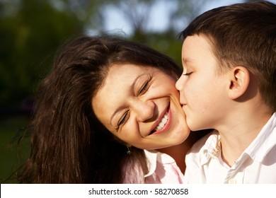 little boy kiss his mother outdoor