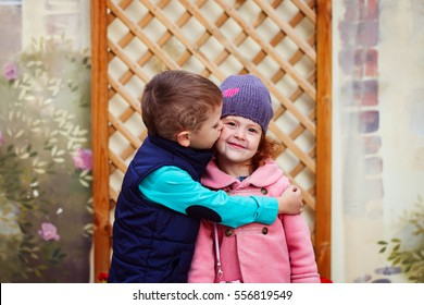 Little boy kissed for the first time adorable little girl. Love and romantic concept.