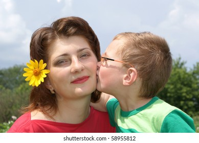 A little boy kisses his mom