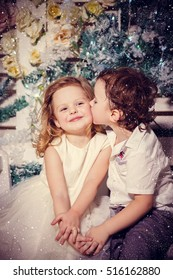Little boy kissing a girl in christmas
