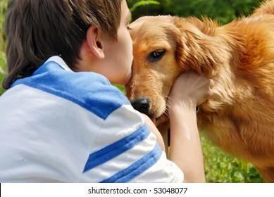 little boy kissing golden retriever dog closeup