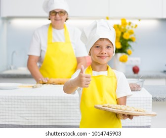 Little boy in the kitchen holds a cooked dumplings in his hands and shows a thumbs-up, grandmom on the background