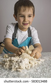 Little boy is kneading raw pizza dough and smiling