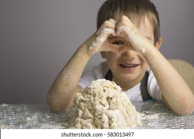Little boy is kneading raw pizza dough and looking through heart shape hands