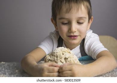 Little boy is kneading raw pizza dough and making a hug