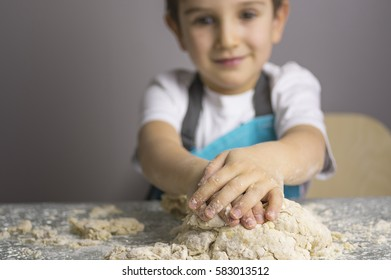 Little boy kneading raw pizza dough. Focus on foreground.