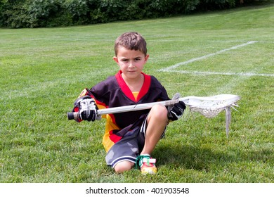 Little boy lacrosse player in the park kneeling down and posing for camera