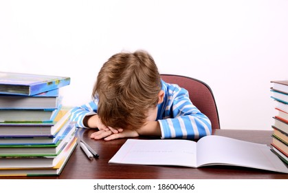 little boy laid his head on the desk on the light background, horizontal