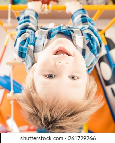 little boy laughing upside down on gym ladder