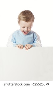 The little boy laughs cheerfully. A boy is holding a white background in his hands. A boy is isolated on a white background.