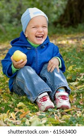 Little boy laughs and sits on the grass, autumn.