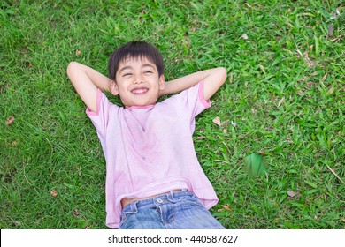 Little boy lay down on the grass with smile face