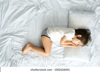 Little boy laying on bed sheets