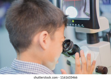 Little boy leaning to use microscope in the science lap at school