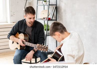 Little boy learn to play guitar while his older brother watches at him