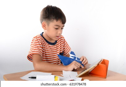 Little boy learning how to Fold a piece of paper by watching tablet how to do