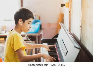 Kleiner Junge, der Klavier spielt und digitale Tablette online spielt