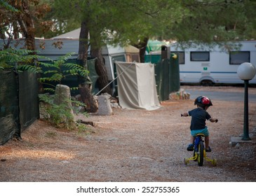 little boy learning to ride a bike in a campsite on holiday