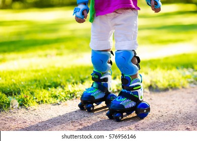 Little boy learning to roller skate in summer park. Children wearing protection pads for safe roller skating ride. Active outdoor sport for kids. Close up view of skates