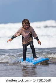 Little boy learning to surf at the beach, getting up on surfboard for the first time, west coast of Ireland