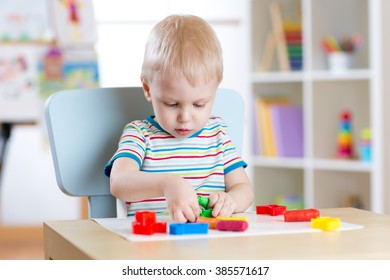 Little boy learning to use colorful play dough in nursery room