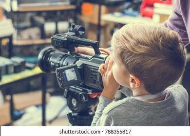 Kleiner Junge, der lernt, digitale Videokamera im Studio zu verwenden.