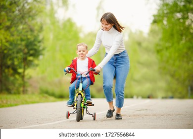 Little boy learns how to ride bicycle, his Mom is happy and laughs success. Concept family, support.