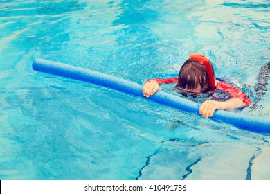 Little boy learns swimming with pool noodle