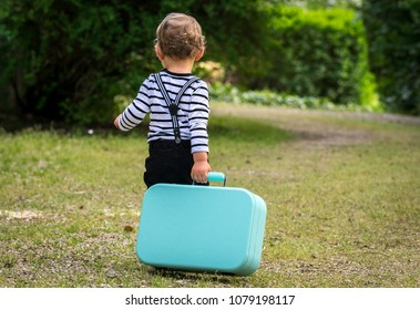 a little boy leaves by dragging a suitcase behind him
