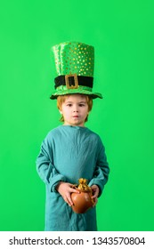 Little boy with Leprechaun hat. Coin. Money. Kid in green costume and leprechaun top hat with golden buckle. Traditions of Saint Patrick Day. Cute boy holds pot of gold. St. Patrick's day celebrations