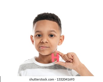Little boy with letter on white background. Concept of speech therapy