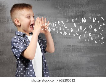 Little boy and letters on grunge background. Speech therapy concept