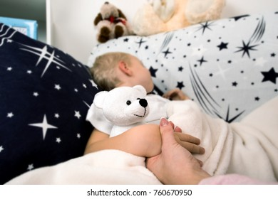 A little boy lies in bed.Mom gently kisses it before to sleep