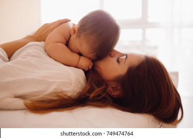 Little boy lies on his mom resting on the bed