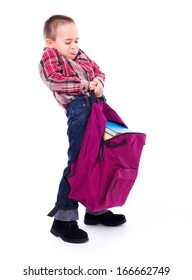 Little boy lifting big, heavy schoolbag full of books