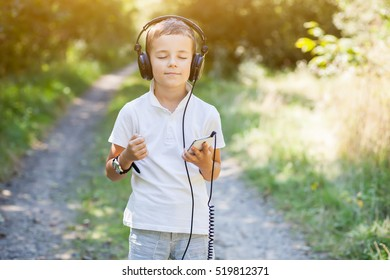 Little boy listening the music with headset in park