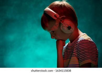 Little boy listens to his favorite music in modern wireless headphones
