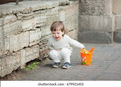 Little boy with long blond hair crying standing on the street. In his hand he is holding an orange bucket to play in the sandbox. Stomach hurts.
