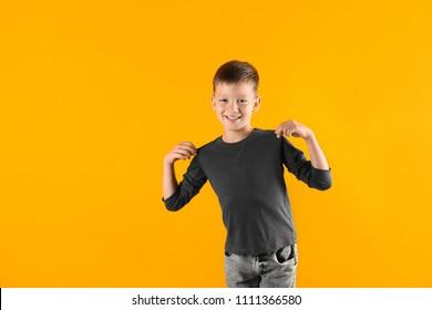 Little boy in long sleeve t-shirt on color background. Mock-up for design