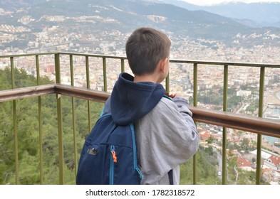 Little boy, looking at the amazing view on the Mediterranian sea gulf with touristic ships and aincient castle and a city from the mountain with a backpack on the back.