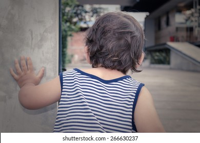 Little Boy Looking Around The Corner of a Little Concrete Wall