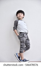 Little boy looking away and standing against white wall : Soft focus