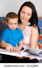 little boy looking in book with his beautiful mother