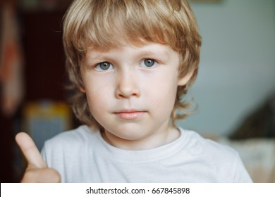 Little boy looking at camera showing thumbs up. Caucasian boy shows thumb up. Boy, thumb up, blonde.