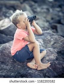 Little boy looking far away with binoculars, sitting on a rock near a sea