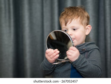 little boy looking at himself in a hand mirror
