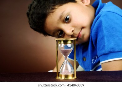 Little boy looking at hourglass