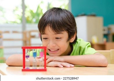 Little boy looking at hourglass in class