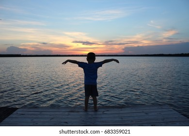 little boy looking at sunset on lake in silhouette