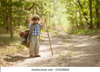 Little boy looking through binoculars while standing on a forest road with a backpack on a warm sunny day